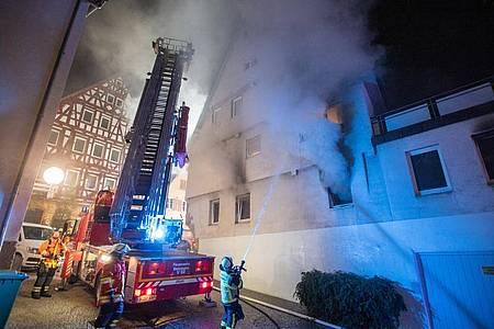 Feuerwehrleute löschen einen Brand in einem Gebäude in der Innenstadt von Marbach. Foto: Simon Adomat/VMD-Images/dpa