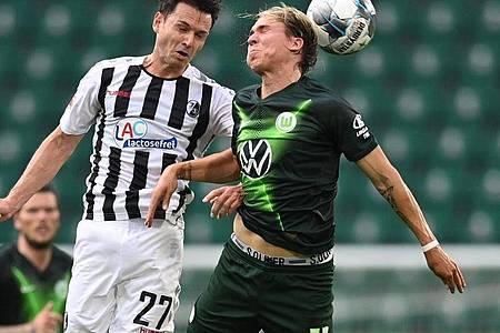 Lucas Höler (l) konnte mit dem SC Freiburg einen Punkt in Wolfsburg ergattern. Foto: Sascha Steinbach/epa Pool/dpa
