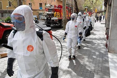 Soldaten in Schutzanzügen in Barcelona sind mit Abstand in Richtung eines Seniorenheims für Desinfektionsarbeiten unterwegs. Foto: David Zorrakino/Europa Press/dpa