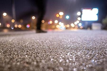 Eis und Graupel bedecken den Gehweh an einer Straßenkreuzung im Stadtteil Bornheim, nachdem bei Temperaturen rund um den Gefrierpunkt Regen einsetzte, der auf den eiskalten Oberflächen gefror. Foto: Frank Rumpenhorst/dpa