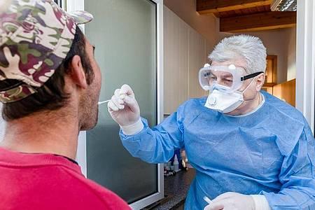 Eijn Arzt führt bei einem Mann in Wesselburen einen Corona-Test durch. Foto: Markus Scholz/dpa