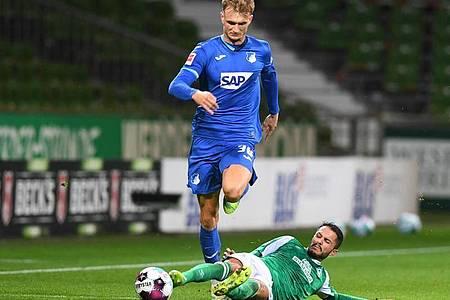 Werders Leonardo Bittencourt (r) versucht Hoffenheims Stefan Posch per Grätsche zu stoppen. Foto: Carmen Jaspersen/dpa