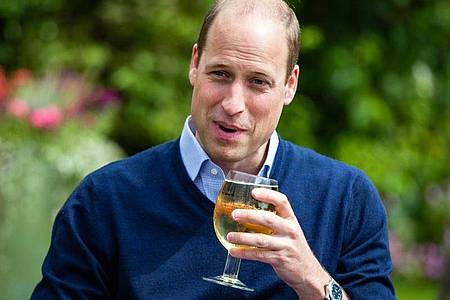 Prinz William hält ein Glas mit Aspalls Cidre bei seinem Besuch im Pub «The Rose and Crown» im Dorf Snettisham. Foto: Aaron Chown/PA Wire/dpa