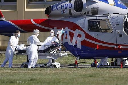 Ein Notfallpatient wird aus dem Zivilkrankenhaus von Mulhouse zu einem Hubschrauber gebracht. Vor allem im Département Haut-Rhin und in der gesamten ostfranzösischen Region Grand Est ist die Zahl der Corona-Infektionen dramatisch gestiegen. Foto: Jean-Francois Badias/AP/dpa