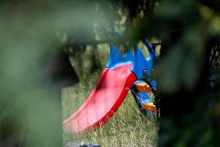 Eine Kinderrutsche ist auf dem Gelände einer Kleingarten-Parzelle zu sehen. Die Polizei ssetzt die Durchsuchung fort. Foto: Peter Steffen/dpa