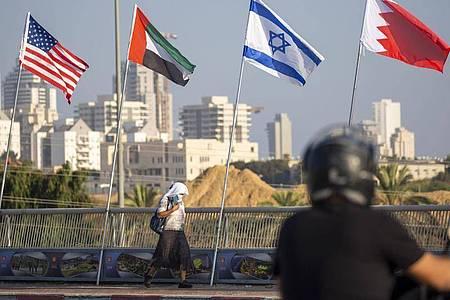 Eine Frau geht an den Flaggen der USA (l-r), der Vereinigten Arabischen Emirate, Israels und Bahrains vorbei. Foto: Ariel Schalit/AP/dpa