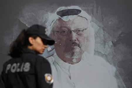 Eine Polizistin geht in der Nähe des saudischen Konsulats in Istanbul an einem Wandbild des ermordeten Journalisten Jamal Khashoggi vorbei. Foto: Lefteris Pitarakis/AP/dpa