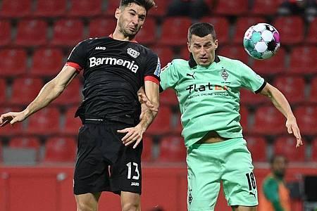 Lucas Alario (l) kämpft mit Mönchengladbachs Verteidiger Stefan Lainer um den Ball. Foto: Ina Fassbender/AFP POOL/dpa