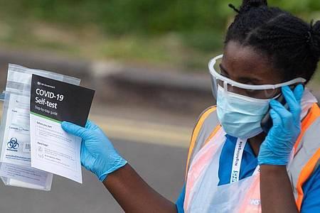 Eine medizinische Mitarbeiterin verteilt Selbsttest-Kits in einem Corona-Testzentrum im Londoner Stadtbezirk Southwark. Foto: Dominic Lipinski/PA Wire/dpa