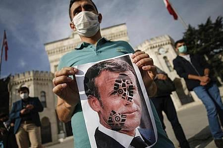 Ein junger Mann hält in Istanbul ein mit einem Schuhabdruck versehenes Foto von Emmanuel Macron in die Kamera. Foto: Emrah Gurel/AP/dpa