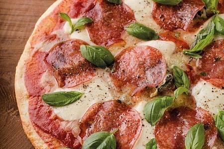 Egal ob mit klassischem Belag oder exotisch: Auf einem Pizzastein gelingt die Pizza auf jedem Grill. Foto: Miriam Primik/Stocker Verlag/dpa-tmn