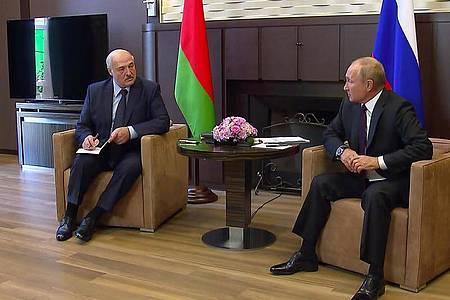 Wladimir Putin (r), Präsident von Russland, unterhält sich mit mit seinem Amtskollegen Alexander Lukaschenko in seiner Sommerresidenz Bocharow Ruchei. Foto: -/Russian Presidential Press Service/AP/dpa