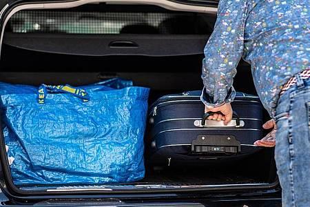 Gepackte Koffer werden in ein Fahrzeug geschoben - doch wo darf ich jetzt noch hinfahren?. Foto: Guido Kirchner/dpa