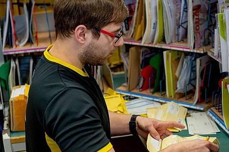 Alexander Seiffert, Fachkraft für Kurier-, Express- und Postdienstleistungen, bei seiner Arbeit im Briefzentrum der Deutschen Post. Foto: Klaus-Dietmar Gabbert/dpa-tmn