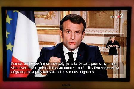 Frankreichs Präsident Emmanuel Macron hält im Fernsehen eine Ansprache: «Der Feind ist da, unsichtbar - und er rückt vor.». Foto: Ludovic Marin/AFP/dpa