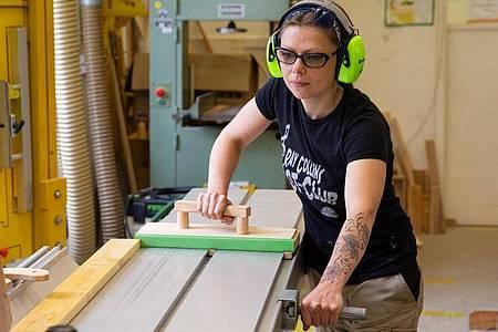 Der Umgang mit den Maschinen will gelernt sein, dafür machen Auszubildende verschiedene Maschinenscheine: Die angehende Tischlerin Marly Konefka nutzt hier die Tischkreissäge. Foto: Catherine Waibel/dpa-tmn