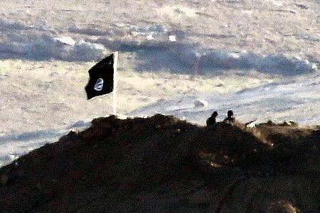 Das Archivfoto zeigt eine Flagge des IS in der syrischen Stadt Kobane. Foto: Sedat Suna/EPA/dpa