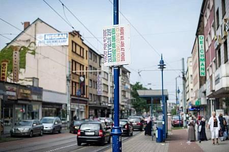 Ein Schild «Hier sind wir zuhause» in verschiedenen Sprachen hängt in Duisburg auf der Straße. Foto: picture alliance / dpa