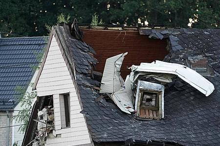 Wrackteile des Kleinflugzeuges ragen aus dem Dach des Wohnhauses. Foto: Thomas Frey/dpa