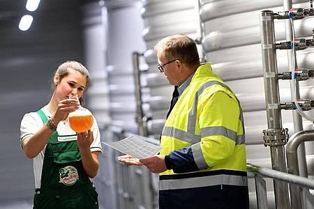 Der Prozess bis zum fertigen Produkt dauert: Die angehende Brauerin und Mälzerin Anna Lautenbacher prüft mit Braumeister Karl-Heinz Silichner eine Märzenprobe in einem Kolben. Foto: Angelika Warmuth/dpa-tmn