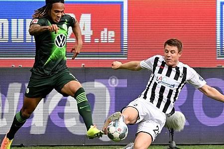 Wolfsburgs Kevin Mbabu (l) im Duell mit Dominique Heintz vom SC Freiburg. Foto: Sascha Steinbach/epa Pool/dpa