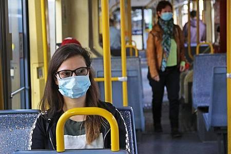 Fahrgäste einer Kölner Stadtbahn tragen Schutzmasken. Foto: Oliver Berg/dpa
