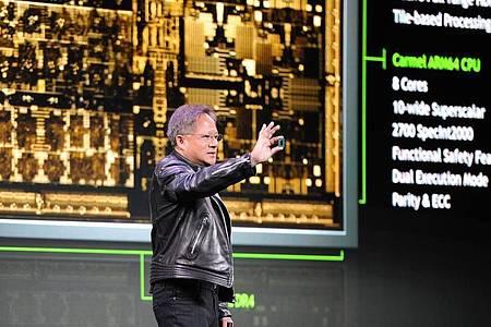 Der Chef des Chipspezialisten Nvidia, Jensen Huang, zeigt 2018 auf der Technik-Messe CES in Las Vegas einen Prototypen des Chips «Drive Xavier» für autonomes Fahren. Foto: Andrej Sokolow/dpa