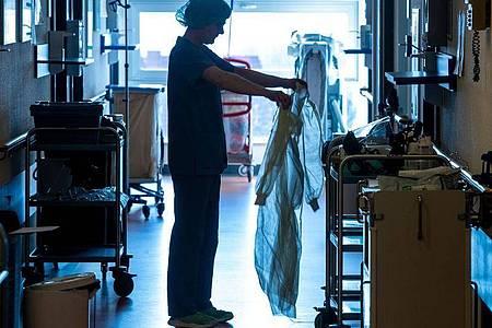 Eine Krankenschwester legt auf einer Corona-Isolierstation Schutzkleidung an. Foto: Jens Büttner/dpa-Zentralbild/dpa