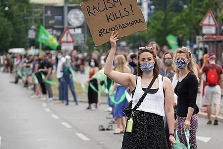 Eine Teilnehmerin in Berlin zeigt das Motto «Black Lives Matter». Foto: Jörg Carstensen/dpa