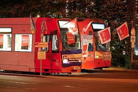 Stadtbahnwagen mit Flaggen der Gewerkschaft Verdi stehen vor einem Depot der Kölner Verkehrsbetriebe (KVB). Durch die Landesweiten Warnstreiks im öffentlichen Personennahverkehr fallen in Köln die Fahrten der Bahn aus. Foto: Henning Kaiser/dpa