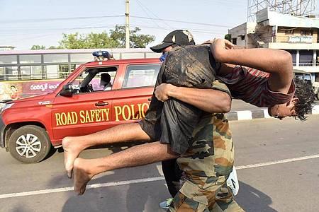 Ein Soldat trägt einen Jungen nach einem Gasunglück an einer Chemiefabrik in Indien. Foto: Uncredited/AP/dpa