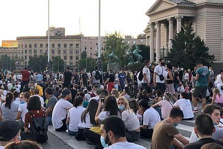 Demonstranten halten eine friedliche Sitzdemonstration in Belgrad ab. Foto: Boris Babic/dpa