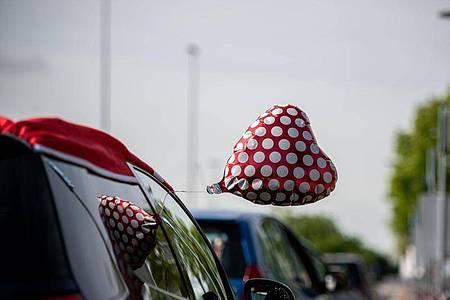 Drei Paare gaben sich im Autokino das Ja-Wort. Ihre Gäste können die Trauung über das Autoradio mithören. Foto: Fabian Strauch/dpa