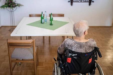 Eine ältere Frau sitzt in einem Pflegeheim in ihrem Rollstuhl vor einem Tisch. Foto: Marcel Kusch/dpa
