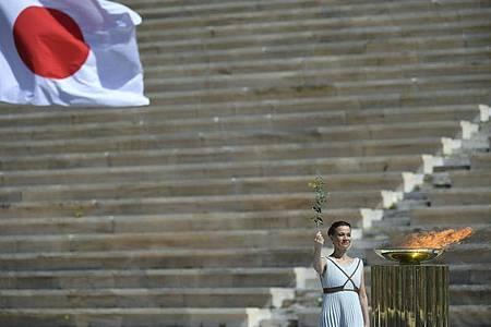 Bei einer kleinen Feier wird das olympische Feuer an die Organisatoren der Sommerspiele von Tokio 2020 übergebe. Foto: Aris Messinis/AFP POOL/AP/dpa