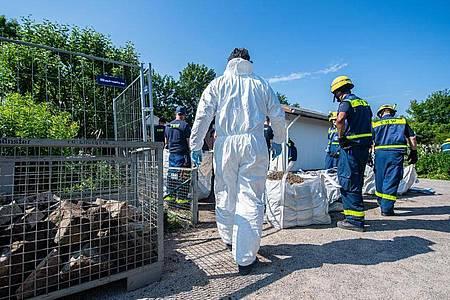Mitarbeiter vom Technischen Hilfswerk (THW) tragen vor dem Abriss der Gartenlaube des Verdächtigen im Missbrauchsfall von Münster einen steinumrandeten Erdhügel ab. Foto: Guido Kirchner/dpa