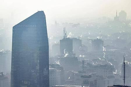 Weißer nebliger Rauch aus Schornsteinen hängt über der Innenstadt von Mailand. Foto: Claudio Furlan/LaPresse/dpa