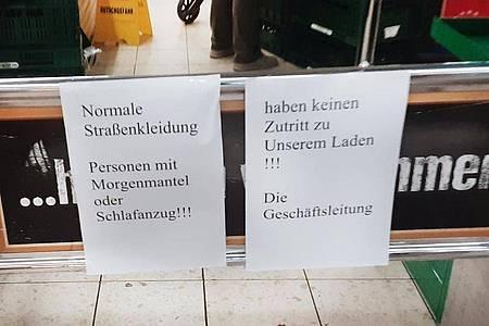 Hinweiszettel machen die Kundschaft in dem Duisburger Supermarkt auf die nun geltende Kleiderordnung aufmerksam. Foto: ---/privat/dpa
