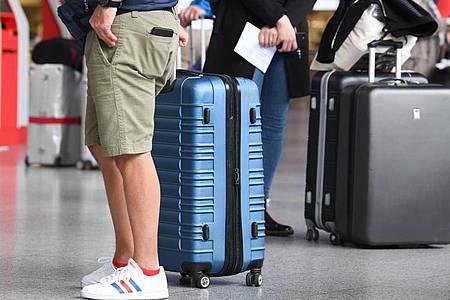 Flugreisende am Check-in-Schalter eines Flughafens. Foto: Arne Dedert/dpa