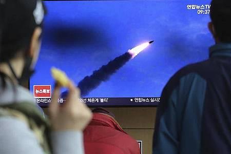 Menschen im Bahnhof von Seoul verfolgen eine Nachrichtensendung, in der über den Abschuss der Raketen berichtet wird. Foto: Ahn Young-Joon/AP/dpa
