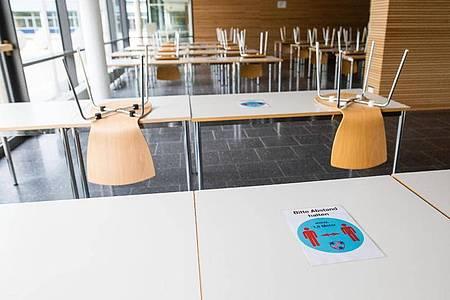 Ein Hinweisschild mit der Aufschrift «Bitte Abstand halten - mind. 1,5m Meter» klebt im Kreisgymnasium in Bad Krozingen auf einem Tisch. Foto: Philipp von Ditfurth/dpa