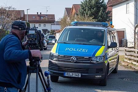 Ein Mannschaftswagen der Polizei steht vor einem Haus in Vogtareuth, in dem drei Tote Menschen aufgefunden worden waren. Foto: Lino Mirgeler/dpa