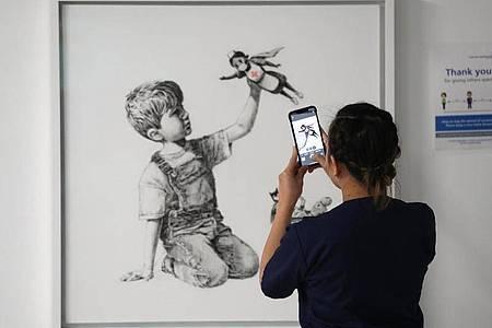 Eine medizinische Mitarbeiterin fotografiert das Banksy-Kunstwerk mit dem Titel «Game Changer». Foto: Andrew Matthews/PA Wire/dpa
