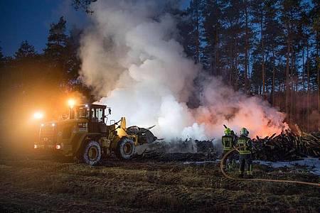 Die Feuerwehr löscht etwa 10.000 Kubikmeter brennende Holzstämme im Landkreis Barnim. Foto: Jörg Carstensen/dpa