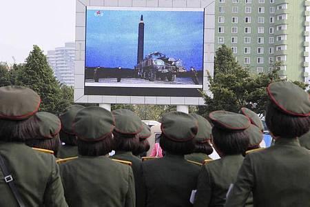 Menschen stehen am 30.08.2017 auf dem Platz vor dem Hauptbahnhof in Pjöngjang, um die Übertragung eines Raketentests zu beobachten. Foto: Kim Kwang Hyon/AP/dpa