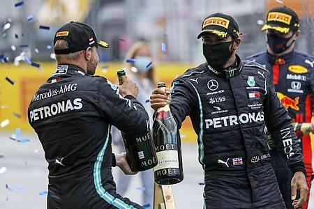Hatten in Spielberg erneut Grund zum Feiern: Lewis Hamilton (r) und sein Mercedes-Teamkollege Valtteri Bottas. Foto: Leonhard Foeger/Pool Reuters/AP/dpa