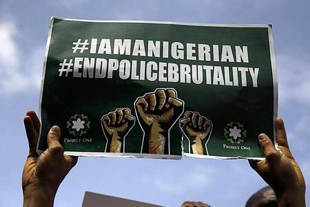 Menschen demonstrieren in Lagos mit Transparenten auf der Straße gegen die Brutalität der Polizei. Foto: Sunday Alamba/AP/dpa