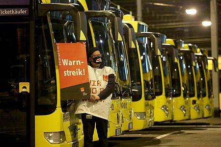 """Ein streikender Busfahrer der Ruhrbahn klebt ein Plakat """"Warnstreik"""" an einen Bus. Foto: Roland Weihrauch/dpa"""