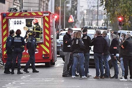 Rettungskräfte und Beamte der Polizei stehen am Tatort, an dem ein griechisch-orthodoxer Priester angeschossen wurde. Foto: Philippe Desmazes/AFP/dpa
