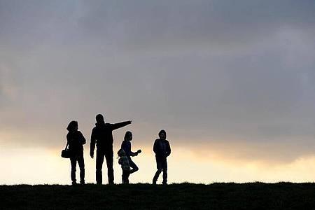 Eine Familie beim Spaziergang unterm abendlichen Wolkenhimmel. Foto: picture alliance / dpa